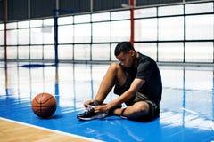 Afroamerikanerteenager, der seine Schnürsenkel auf einem Basketballplatz bindet lizenzfreie stockbilder