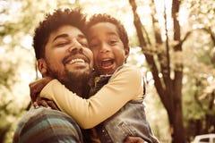 Afroamerikanervater, der kleine Tochter im Park umarmt stockfotos