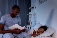 Afroamerikanervater-Lesebuch für schlafende Tochter stockbild