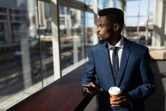afroamerykański biznesmen patrzeje daleko od w biurze z filiżanką i telefonem komórkowym fotografia stock