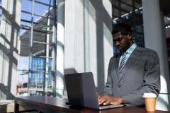 afroamerykański biznesmen z filiżanką używać laptop w biurze obrazy stock