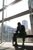 afroamerykański biznesmena obsiadanie na ławce i używać telefon komórkowy w biurze zdjęcia stock