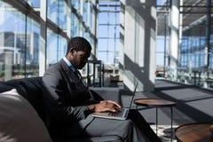 afroamerykański biznesmena obsiadanie na używać laptopie w nowożytnym biurze i kanapie zdjęcie stock