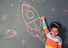 afroamerykański dziecko bawić się z kredy rakiety rysunkiem zdjęcie royalty free
