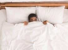 Afroamerykański mężczyzna w łóżku chuje pod koc fotografia royalty free