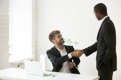 Afroamerykański szef gratuluje caucasian pracownika z pro zdjęcie stock