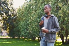 Afroamerykański uczeń z bierze oddaloną kawę w parku outdoors zdjęcia royalty free