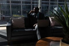 Afroamerykanin biznesmen opowiada na telefonie komórkowym na kanapie w biurze z laptopem fotografia stock