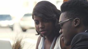 Afrobeambten die met laptop computer hoge vijf in openluchtkoffie maken stock video