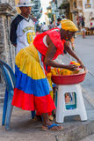 Afrocaribbean woman selling fresh choped fruit in. CARTAGENA, COLOMBIA - FEBRUARY 25, 2015: Afrocaribbean woman wearing a colorful dress selling fresh choped Royalty Free Stock Photos