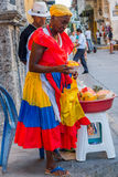 Afrocaribbean woman selling fresh choped fruit in. CARTAGENA, COLOMBIA - FEBRUARY 25, 2015: Afrocaribbean woman wearing a colorful dress selling fresh choped Stock Photo