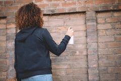 Afroe-amerikanisch Frau, die Sprühfarbe verwendet Stockbild