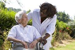 Afroe-amerikanisch Pflegekraft, die mit einer behinderten älteren Frau spricht stockfotografie
