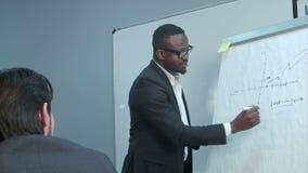 Afroer-amerikanisch Geschäftsmann, der Darstellung von einem Unternehmensplan auf dem flipchart macht stock footage