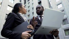 Afroer-amerikanisch Geschäftsmann, der dem Assistenten Anweisungen, arbeitend an Projekt erteilt lizenzfreies stockfoto