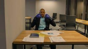 Afroer-amerikanisch Geschäftsmann, der mit Boxhandschuhen im Büro sitzt stock video footage