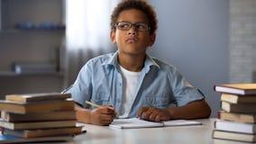 Afroer-amerikanisch Junge, der auf Schulversuch, intelligentes Kind tut Hausarbeit, Bildung denkt stockbild