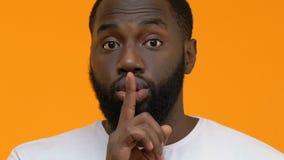 Afroer-amerikanisch Kerl, der macht, die Gestennahaufnahme, bitten zum Schweigen zu bringen, ruhig zu sein, Verschwörung stock video