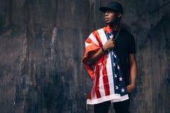 Afroer-amerikanisch Kerl mit US-Flagge auf dunklem Hintergrund Stockbild