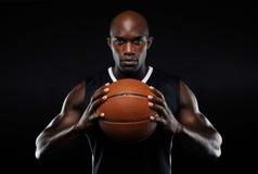 Afroer-amerikanisch männlicher Basketball-Spieler mit einem Ball Stockfoto