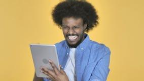 Afroer-amerikanisch Mann aufgeregt für Erfolg während unter Verwendung des Tablets auf gelbem Hintergrund stock video footage