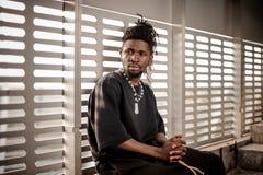 Afroer-amerikanisch Mann, der auf dem Fensterbrett sitzt lizenzfreies stockfoto