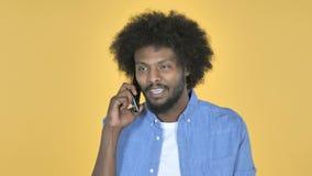 Afroer-amerikanisch Mann, der auf Smartphone auf gelbem Hintergrund spricht stock footage