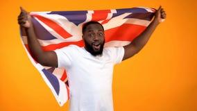 Afroer-amerikanisch Mann, der britische Flagge, Unterst?tzungswahlsieger, diplomatisch h?lt stockfotografie