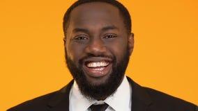 Afroer-amerikanisch Mann, der nett in die Kamera, glücklich über erfolgreiche Idee lacht stock video