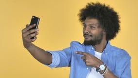 Afroer-amerikanisch Mann, der Selfie mit Smartphone auf gelbem Hintergrund nimmt stock video