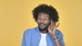Afroer-amerikanisch Mann-hörende geheime Stellung auf gelbem Hintergrund stock footage