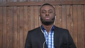 Afroer-amerikanisch Mann im Anzug und im Hemd ist hörende Musik stock video footage