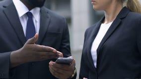 Afroer-amerikanisch Rechtsanwalt, der späteste Nachrichten mit dem Kollegen, Smartphone halten bespricht stock video footage