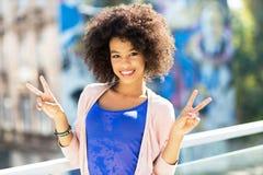 Afrofrau, die ein Friedenszeichen gibt Lizenzfreie Stockfotografie