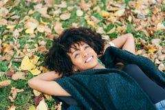 Afrofrisurenfrau, die im Herbst daydraming ist stockfoto