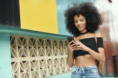 Afrohaar der schwarzen Frau auf der Straße, die einen Smartphone hält Lizenzfreies Stockfoto