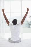 Afromann, der im Bett aufwacht und seine Arme ausdehnt Stockfotografie