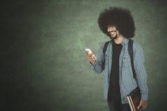 Afromens die zijn smartphone bekijken Stock Afbeelding