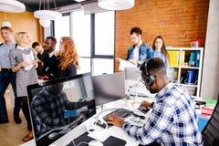 Afrosekretär mit den Kopfhörern, die vor Computer arbeiten stockbilder