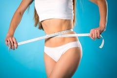 Afrouxando o peso - a jovem mulher está medindo sua cintura Imagens de Stock