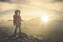 Afrowandelaar op de berg tijdens zonsopgang stock foto's