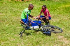 Afrykańscy dzieci załatwia dziurawienie na rowerze obraz stock