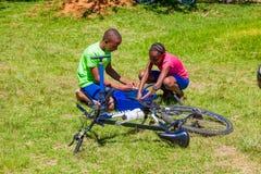 Afrykańscy dzieci załatwia dziurawienie na rowerze zdjęcie royalty free