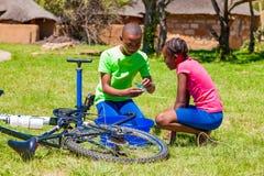 Afrykańscy dzieci załatwia dziurawienie na rowerze zdjęcia royalty free