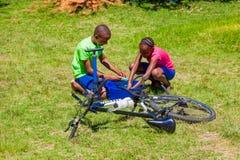 Afrykańscy dzieci załatwia dziurawienie na rowerze obrazy stock
