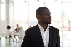 Afrykańska biznesmen pozycja w biurowy myślący patrzeć daleko od zdjęcia stock