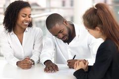 Afrykański biznesmena obsiadanie przy biurkiem z różnorodnymi pracownikami podpisuje kontrakt fotografia stock