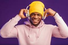 Afrykański mężczyzna w hoodie z hełmofonami odizolowywającymi, szczęśliwy wyrażenie Muzyka, ludzie obrazy stock