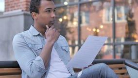Afrykańscy mężczyzny czytania dokumenty podczas gdy siedzieć plenerowy zbiory wideo