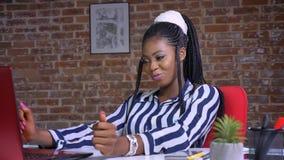 Afrykańska ładna dziewczyna ma relaksującego tana w ceglanym studiu podczas gdy siedzący przy pracującym stołem zbiory